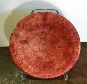 This shallow bowl was dyed with a blood red analine dye to bring out the grain in the beautiful maple Burl.  Once dyed it is sanded with 400 grit sand paper.  This process enhances the grain.